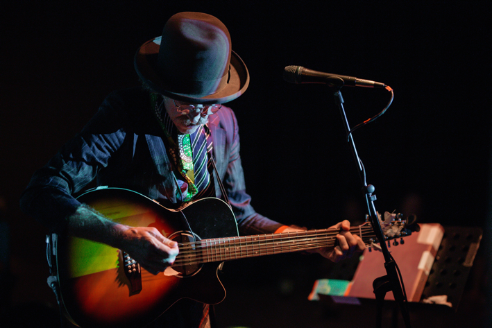 Artist Martin Creed playing the guitar on stage
